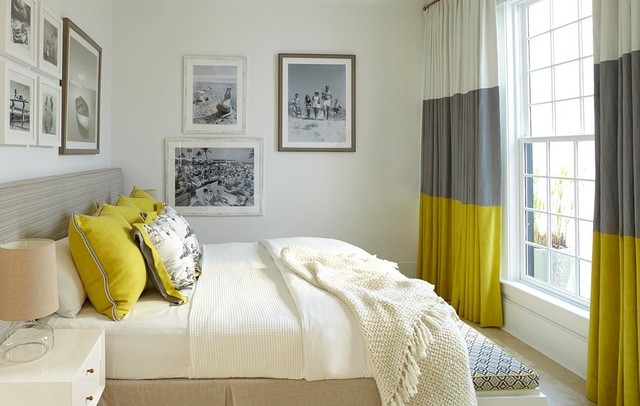 On the right of the picture are floor to ceiling length, curtains. The three colours are white, medium grey and acid yellow at the bottom of the curtain. On the left of the image are acid yellow cushions on the bed.