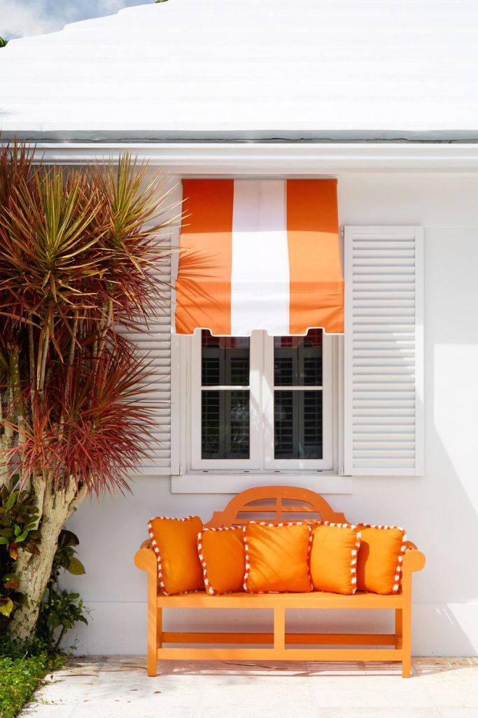 Exterior view of orange and white awning over a window which has shutters on either side of the window. There is an orange, two seater bench with orange cushions. The bench is in front of the window.