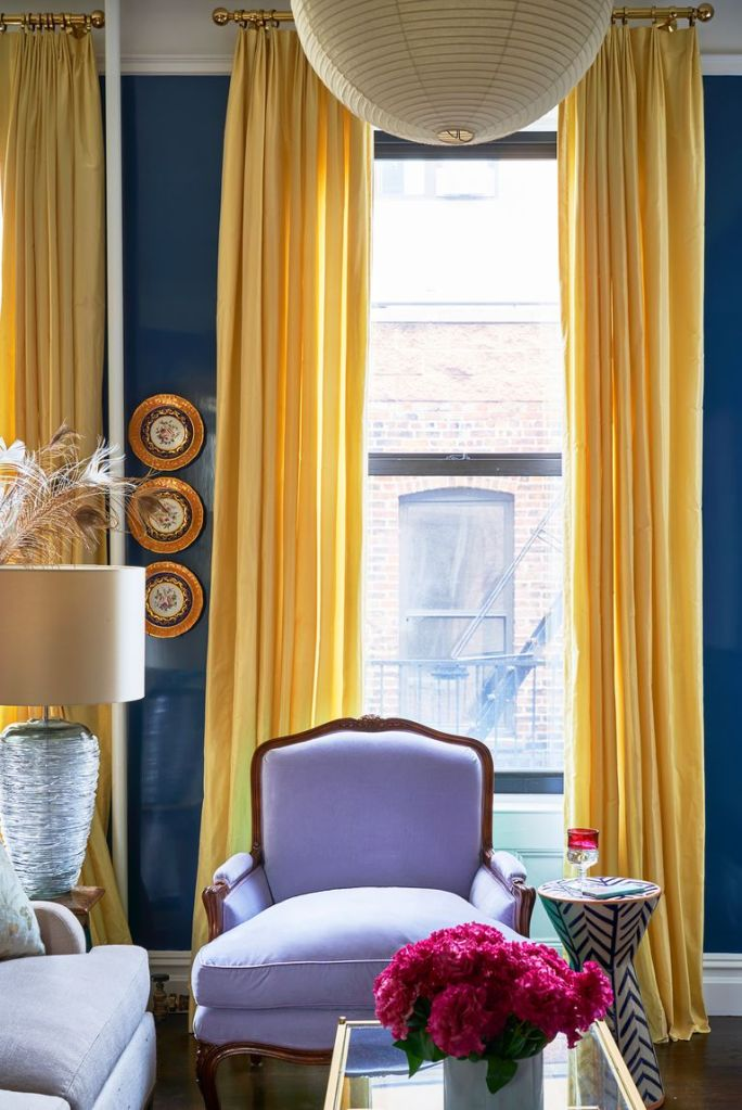 There is a full height window with full length yellow curtains. The wall is painted a dark, pastel blue colour. There is a single wooden frame chair with pale lilac fabric finish.
