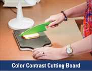 The brown counter top contrast in colour to the black cutting board. The slice of white bread contrasts on the cutting board to the black cutting board and lime green knife.
