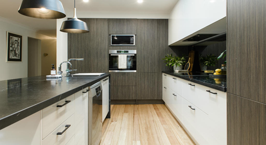 The kitchen floor is a light coloured wooden strip floor.Left and right in the image the kitchen cupboards and drawer fronts are white with black pull handles. The counter top is black marble. The central back wall is a dark wood finish. There are recessed down lights in the ceiling for general lighting. There is under counter lighting on the right. On the left the island unit has two large dark gray feature pendent lights suspended over the unit.