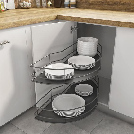 Image shows an open corner cupboard with the accessible basket attached to the open door. The corner cupboard is storing a set of plates, side plates soup bowls, pudding bowls. White coloured crockery on a dark grey solid base and wire sides.