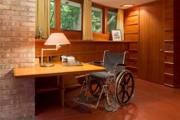 On the left is a wall finished in brickface with a light timber desk wrapped around it. There is a wheelchair at the desk. The floor is finished with ceramic tiles. The walls have built in drawers below the window and wooden cladding and door, all finished the the same colour timber.