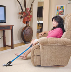 Image shows a lady sitting in an upholstered armchair using a reacher. A reacher is an aluminium rod with pinchers on the end used to pick up a remote that has fallen onto the floor.