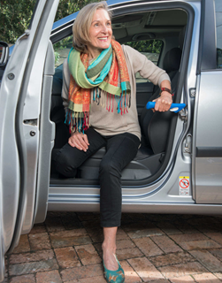 A lady is getting out of a car. The car door is open. The lady has her left hand on an assistive handle which is hooked into the door lock loop. Her left hand foot is on the ground and she is swiveling into a position to lift her right hand foot out of the car onto the ground. And ultimately lift herself up off the seat into a standing position.