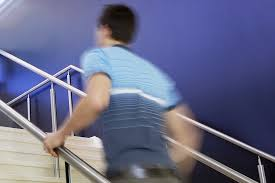 Image shows a man in a blue striped shirt running up a flight of stairs, while holding on the handrail. To show the man is running the image of him is blurred and the handrail and stairs not.