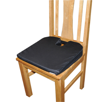 A memory foam pressure cushion placed on the seat of a wooden chair.