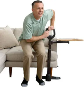 A man is in the process of standing up from a couch. He has both his hands on a single leg couch support, on left hand side. The support has a large round/ square shape to accommodate a two handed grip. On the left and attached to the support is a side table, which can be swiveled and used when sitting down. The linear flat foot is secured under the foot of the couch.