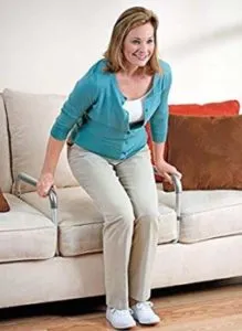 A lady is lifting herself up from a seated position on the 'armless' couch. A two leg couch assist provides her with handles that she can use to push up into a standing position.