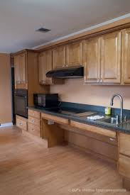 Image shows wall elevation of a floor to ceiling built in accessible kitchen. The kickplate is enlarged. There is a recess below the hob and sink units. The Oven is positioned at a lower height. The sink tap is positioned on the side. There are wall cupboards which are out of reach unless there are pull down shelves. The cabinetry is natural wood. The counter top is black granite.
