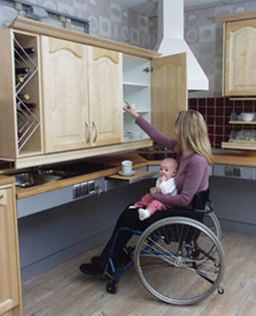 The wall cupboards is made up of a wine rack and three 700mm wide cupboards. The lady seated in a wheelchair has a baby on her lap and is taking items out of the lowered cupboard. There is also an additional surface which has been pulled out. there is a cup and saucer on it. The pull down unit is above the double bowl sink.