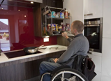 There is a man sitting in a wheelchair in front of a cooking hob. He has his hand on the pull down shelf containing spices. The counter top is white. The cabinetry is grey-brown wood combination and the splash back behind the counter is a maroon gloss finish.