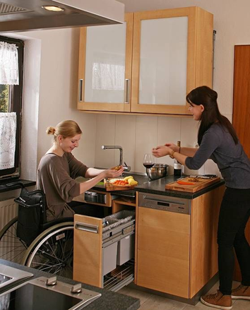 There are two ladies preparing vegetables at the sink. The lady on the left is in a wheelchair pulled up underneath the sink. The pull out drawer has two rectangular bins in it. The lady on the right is standing. The cabinetry is natural timber and black granite counter top.