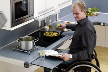 Image shows a man sitting in a wheelchair looking at a recipe book and stirring the pot on the stove. The additional pull out surface is being used.